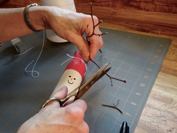 adding wood twig arms to snowman Christmas cracker