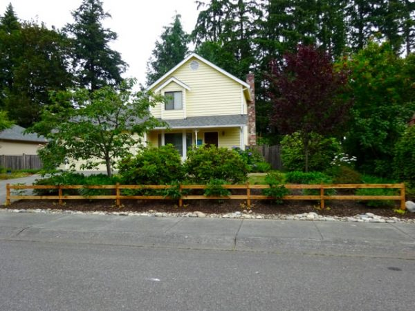Two rail wood fence in front of a house