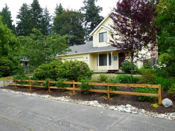 Two rail wood fence in a garden in front of a house