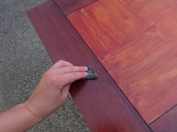 Sanding a wood table between coats of stain