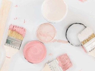 jars of pink paint samples with brushes on white background