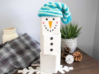 painted wood block Snowman with blue cap on table