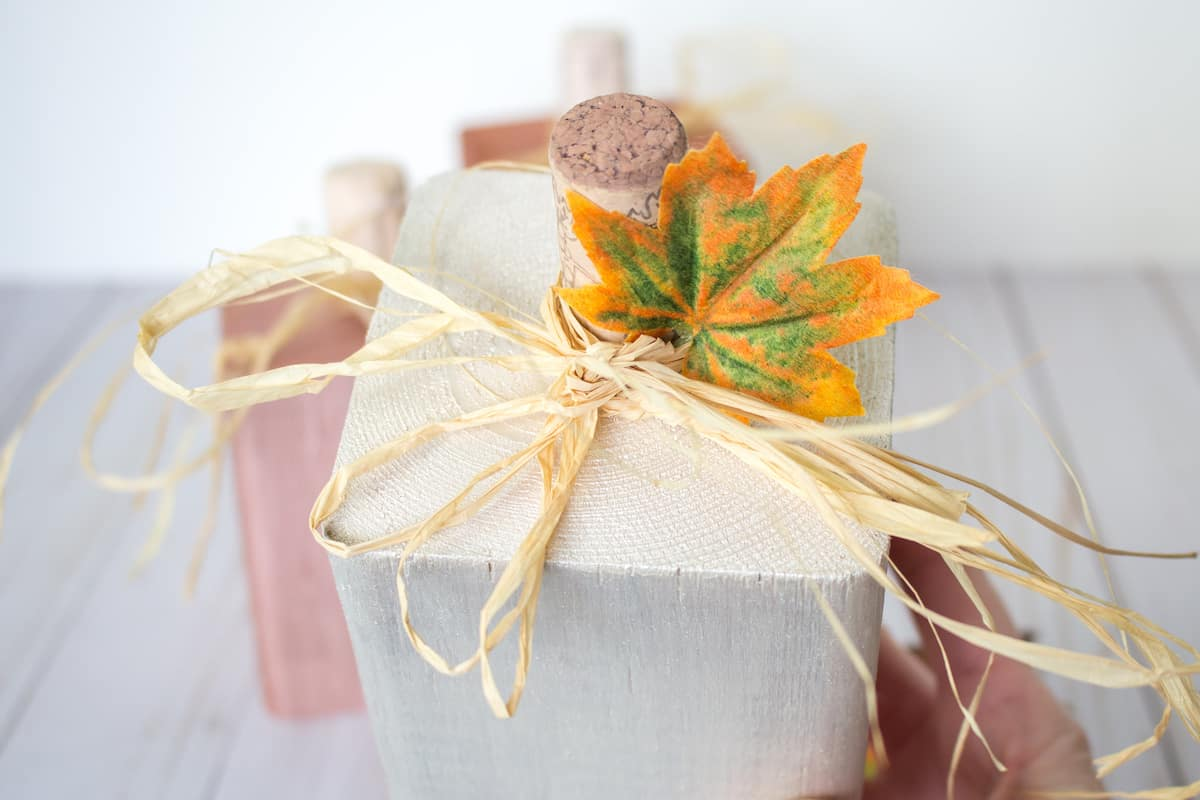 paper tied bow atop wood block pumpkin