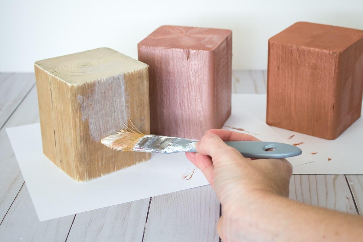 applying metallic paint to wood block pumpkins