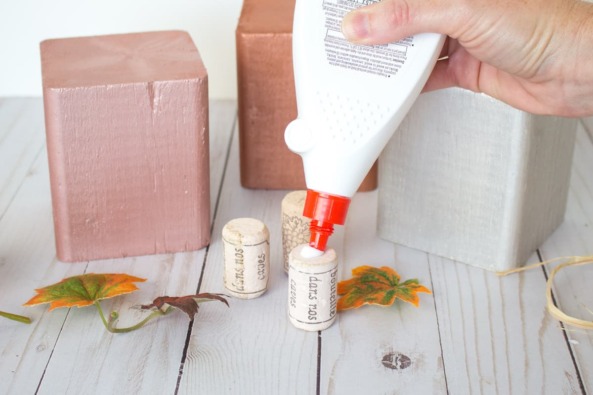 applying glue to cork stem to for wood block pumpkin