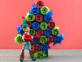 Christmas elf next to homemade advent calendar against pink backdrop