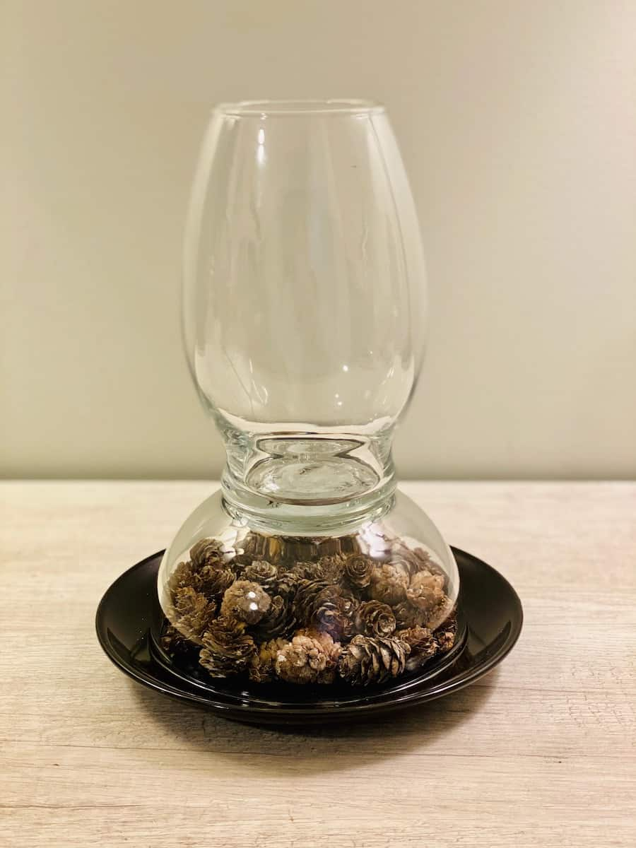 DIY Hurricane glass Lamp over black plate filled with Pinecones