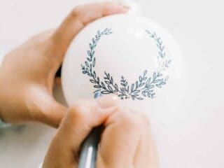 woman painting a Christmas ornament