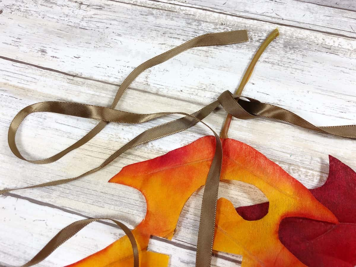 Tying ribbon to fall banner craft