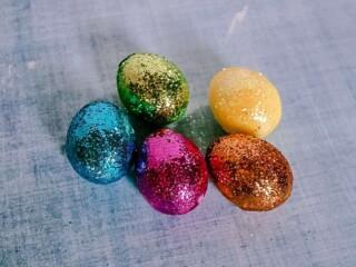 DIY Glitter Easter eggs on blue background