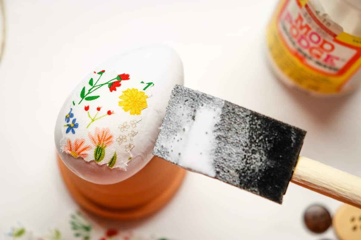 applying Mod Podge to fabric covered egg