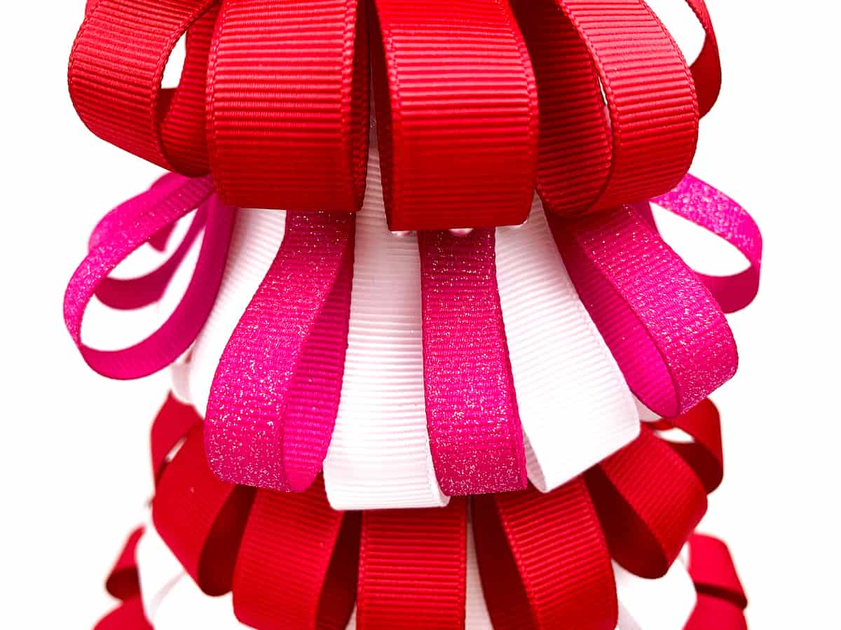 pink ribbon loops among white and red loops on a styrofoam tree