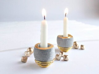 small cement candleholders with burning taper candles
