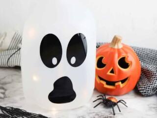 easy to make milk jug ghost luminary in front of Halloween pumpkin